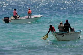 In this March 3, 2008 photo, environmental workers collect sea samples after an oil spill at Boca Chica, Dominican Republic.