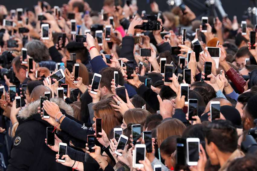People use their smartphones to take photos of the Pope in Paris, France, Oct. 1. MissioBot is available for the entire month of October in commemoration of World Mission Sunday, Oct. 22.