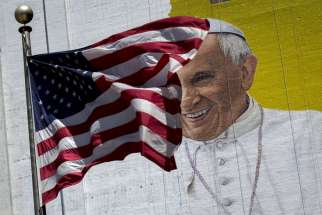 "The U.S. flag flies in front of a mural of Pope Francis in New York City. Pope Francis' 10th foreign trip will be the longest of his pontificate and, with stops in Cuba, three U.S. cities and the United Nations, it also will be a ""very complex trip,"" the papal spokesman said."