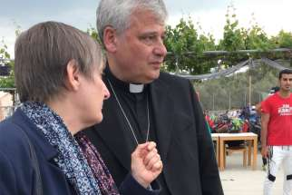 Daniela Pompei confers with Cardinal Konrad Krajewski, the papal almoner, during a May 2019 visit to the Moria refugee camp on the Greek island of Lesbos. The cardinal has tested positive for COVID-19 and is hospitalized.