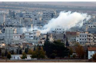 A view shows smoke rising Nov. 20 from a Kobani, Syria, neighborhood damaged by fighting between Islamic State militants and Kurdish forces.