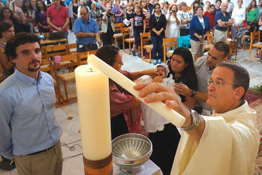 Jesuit Father David Neuhaus lights a baptismal candle during a Mass for Hebrew-speaking Catholics in Israel in 2014.