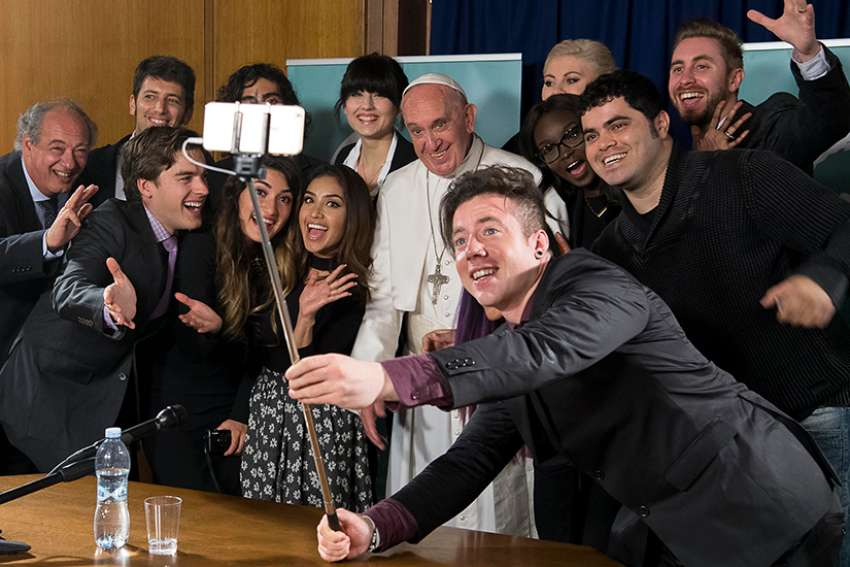 "Pope Francis poses for a selfie picture during a meeting of the Scholas Occurrentes at the Vatican May 29. The Scholas Occurrentes organization, which the pope also supported as archbishop of Buenos Aires, Argentina, promotes a ""culture of encounter"" through art, sports and technology."
