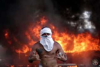 An opposition demonstrator gestures while carrying stones in front of a burning bus during a violent protest near Carlota airbase in Caracas, Venezuela, April 30, 2019. Armored vehicles plowed into anti-government protesters as troops loyal to Venezuelan President Nicolas Maduro tried to restore order; opposition leader Juan Guaido took to the streets in an attempt to lead a military uprising against the embattled president.