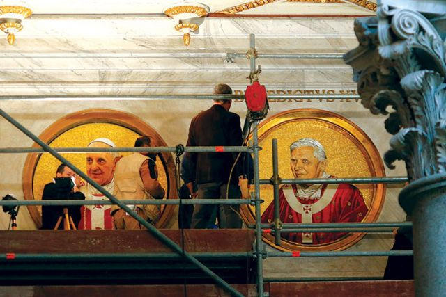 Workers install a mosaic depicting Pope Francis next to the one depicting Pope Benedict XVI in St. Paul's Basilica in Rome Dec. 9.