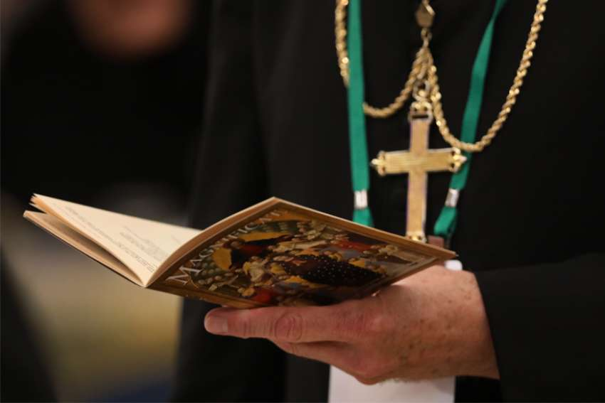 A bishop prays on the first day of the annual general assembly of the USCCB in Baltimore June 11, 2019.