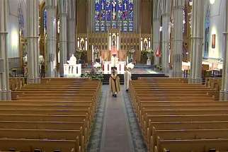 Cardinal Thomas Collins walks up the aisle at an almost-empty St. Michael's Cathedral Basilica to open the broadcast of Easter Sunday Mass. The broadcast was viewed in more than 55,000 homes.