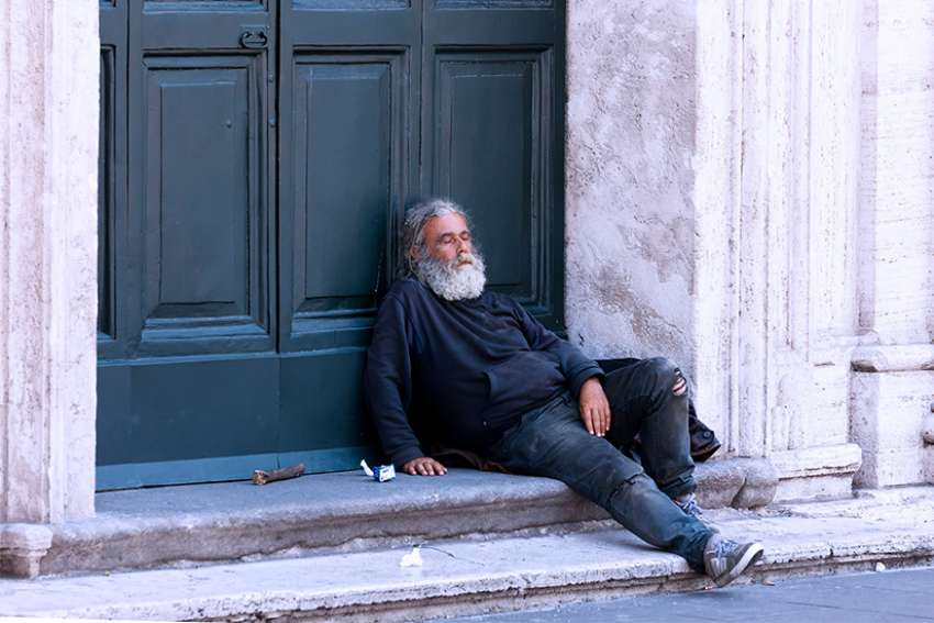 A homeless man rests outside a church in Rome, 2014.