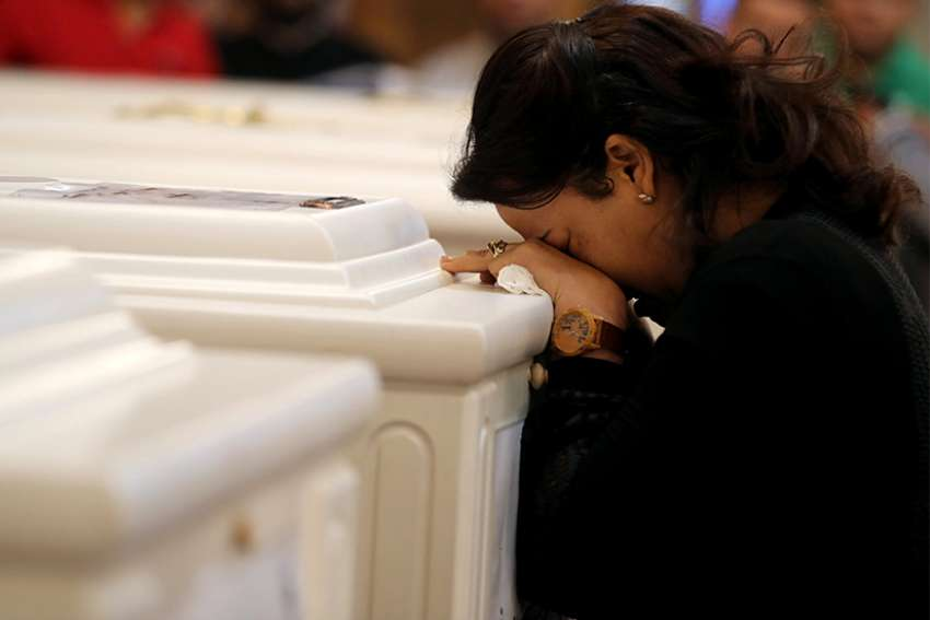 A woman mourns during a Nov. 3 funeral Mass at Prince Tadros Orthodox Church in Minya, Egypt, for a group of Christian pilgrims killed by gunmen as they headed to a monastery Nov. 2.