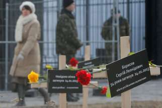 Ukrainians walk past symbolic crosses set up by protesters in front of the Russian embassy in Kiev, Ukraine, Feb. 1.
