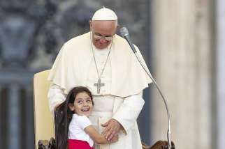 A young girl smiles as she embraces Pope Francis during an audience for families participating in the pastoral conference of the Diocese of Rome in St. Peter's Square at the Vatican June 14.