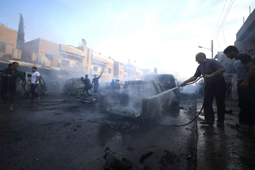 A man sprays water at the site of a car bomb blast in Qamishli, Syria, Oct. 11, 2019. Church bells have been ringing in Qamishli and elsewhere in northeastern Syria, signaling the alarm to Christians and others of the ongoing Turkish military operation having a devastating humanitarian impact on civilians.