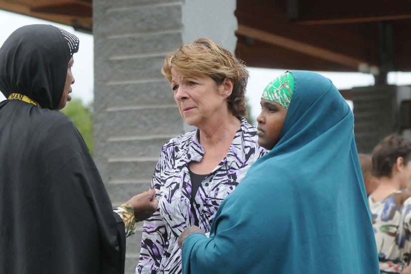 Kathy Langer, director of social concerns for Catholic Charities of the Diocese of St. Cloud, Minn., centre, talks with Maryan Ahmed and Fatumo Ukash following a Sept. 18 news conference organized by the local Somali-American community in St. Cloud after a knife-wielding man injured nine people the previous day at a shopping mall. Bishop Donald J. Kettler of St. Cloud called for prayers for those impacted by the violence.