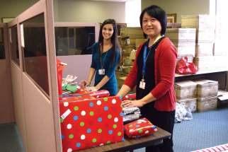 CFS Hamilton staff members Chantelle Pavao and Christine Wong help wrap and organize Christmas gifts for this year's Miracles on Main Street drive.