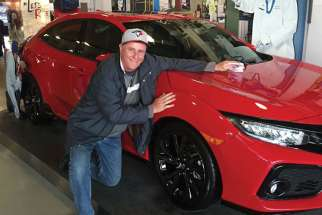 Bob Brehl gets up close with the Honda sports car he won in a raffle at Jays Care.