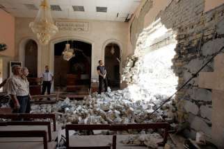 Residents inspect the damage inside St. Ephrem Syrian Orthodox Church after a bomb attack in central Kirkuk, Iraq in this 2011 photo.