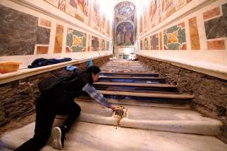 Mei Wen touches an area of the Holy Stairs where Jesus is believed to have fallen during restoration work at the Pontifical Sanctuary of the Holy Stairs in Rome.
