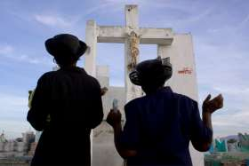Women are pictured in a file photo praying on All Souls' Day, Nov. 2, at a cemetery in Port-Au-Prince, Haiti. Because of the COVID-19 pandemic response measures restrict most gatherings, the Vatican has extended the usual plenary indulgence to souls in purgatory from just the first week in November to include the entire month.