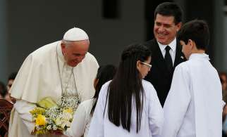 Pope Francis receives flowers at Silvio Pettirossi International Airport in Asuncion, Paraguay, July 10.