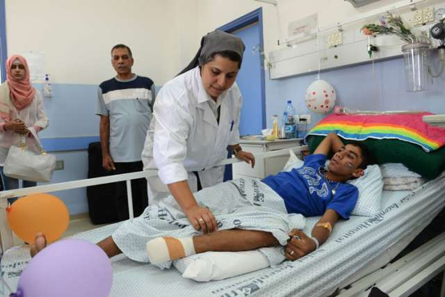 Sister Muna Totah, a member of the Sisters of St. Joseph of the Apparition, works on Karim Nofal, 15, of Gaza, at St. Joseph Hospital in Jerusalem July 30. The teenager is one of 23 Gaza patients being treated at the hospital, which specializes in head- and chest-trauma wounds.