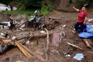 A woman gestures as residents shovel to recover belongings from their house damaged after Tropical Storm Earl caused a mudslide in Huauchinango, Mexico, Aug. 7. Forty people were killed.