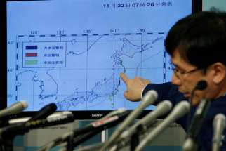 Koji Nakamura, earthquake and volcano observations division director of the Japan Meteorological Agency, points at a map showing earthquake information during a news conference in Tokyo Nov. 22.