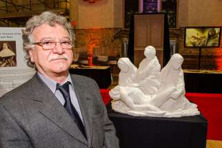 Lawrence Voaides-Cajabn posing with a model of Pietà December 2015. The final marble statue arrived at St. Michael's Cathedral's crypt Nov. 19.