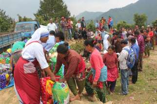 A member of the Missionaries of Charity helps distribute relief items to earthquake victims May 16 in the mountains overlooking Kathmandu Valley in Nepal.