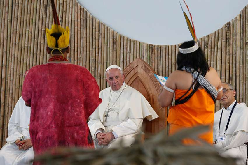 Pope Francis listens to members of an indigenous group from the Amazon region during a Jan. 19 meeting at Madre de Dios stadium in Puerto Maldonado, Peru.