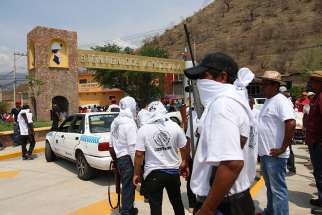A group of armed civilians is seen May 28 in the southern Mexican state of Guerrero. Bishops in Guerrero have suffered threats from organized criminal groups as they serve a region rife with drug cartel activities and parishes located in impoverished indigenous communities where people eke out existences by cultivating opium poppies.