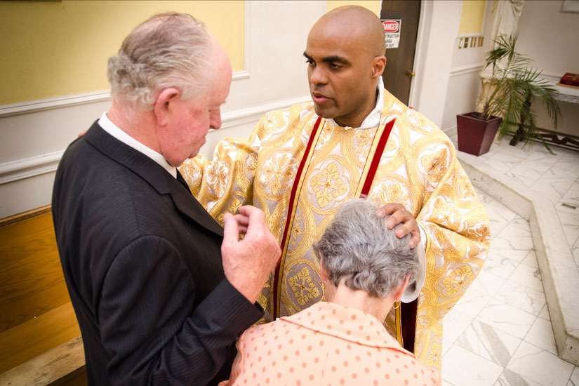 Fr. Ricardo Davis blesses well-wishers after he was ordained to the priesthood May 9 at St. Michael's Cathedral.