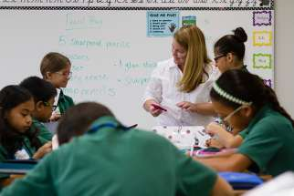 A fifth-grade teacher helps her students organize their supplies on the first day of school Aug. 8 at St. Helen Catholic School in Pearland, Texas.
