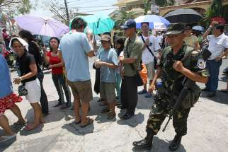 A Philippine air force trooper walks past voters lining up outside a precinct on election day in 2010 in Las Pinas. Archbishop Socrates Villegas of Lingayen-Dagupan is urging Catholics to heed the Ten Commandments before they head to the polls in May to vote for offices ranging from president to local village councillors.