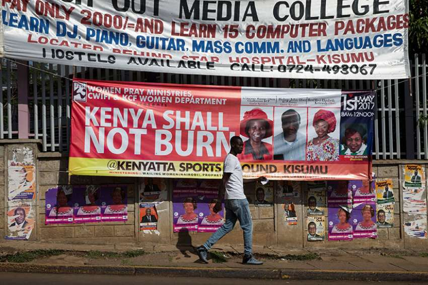 A man walks past a banner calling for prevention of violence during the primary elections April 20 in Kisumu, Kenya.