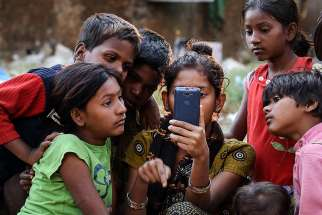 "Indian children watch a movie on a cellphone on the roadside in Mumbai Jan. 20, 2016. While digital communications and social media can be used as a tool of evangelization and a place of dialogue with others, they also can be lonely environments where young people fall prey to humanity's worst vices, Pope Francis wrote in his new apostolic exhortation to young people, ""Christus Vivit"" (""Christ Lives"")."