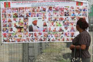 A woman in Bayelsa, Nigeria, reads a Nigerian army poster picturing wanted Boko Haram suspects May 19.