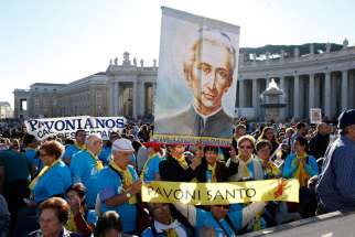 Pilgrims hold a banner of new St. Ludovico Pavoni before the canonization Mass for seven new saints celebrated by Pope Francis in St. Peter's Square at the Vatican Oct. 16.