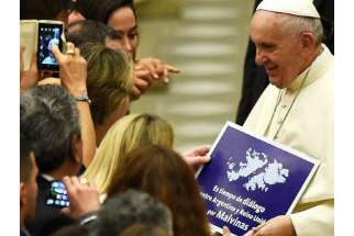 Pope Francis is handed a sign urging dialogue about the ownership of the Falkland Islands.