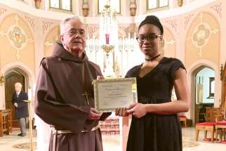 Franciscan Fr. Damian MacPherson awarded Ruthann J. Lemonius her second-place certificate and a new Kobo Aura H2O eReader for her winning essay.