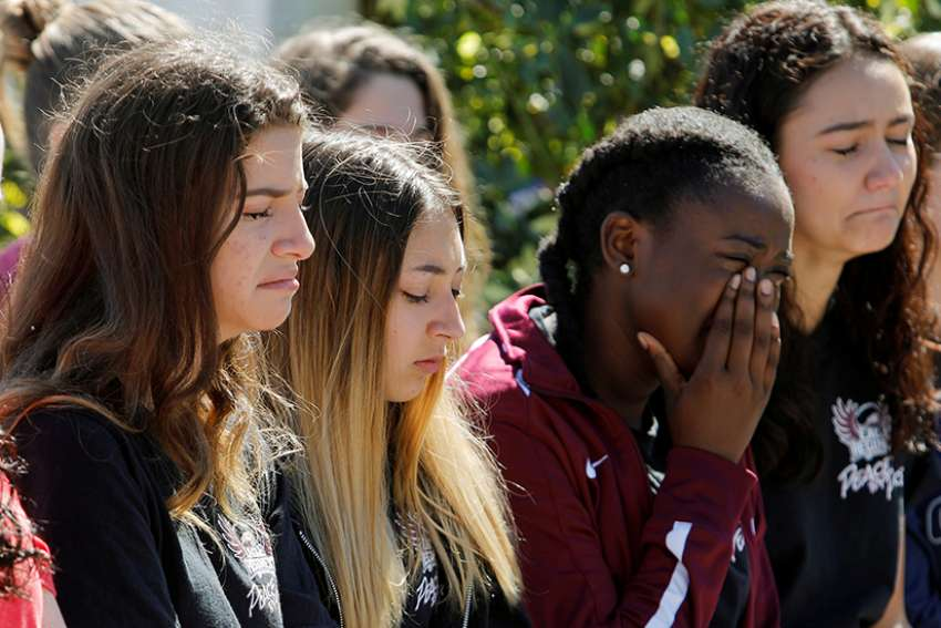 Students mourn during a Feb. 15 prayer vigil in Pompano Beach, Fla., for victims of the shootings at nearby Marjory Stoneman Douglas High School in Parkland. At least 17 people were killed in the shooting. The suspect, 19-year-old former student Nikolas Cruz, is in custody.