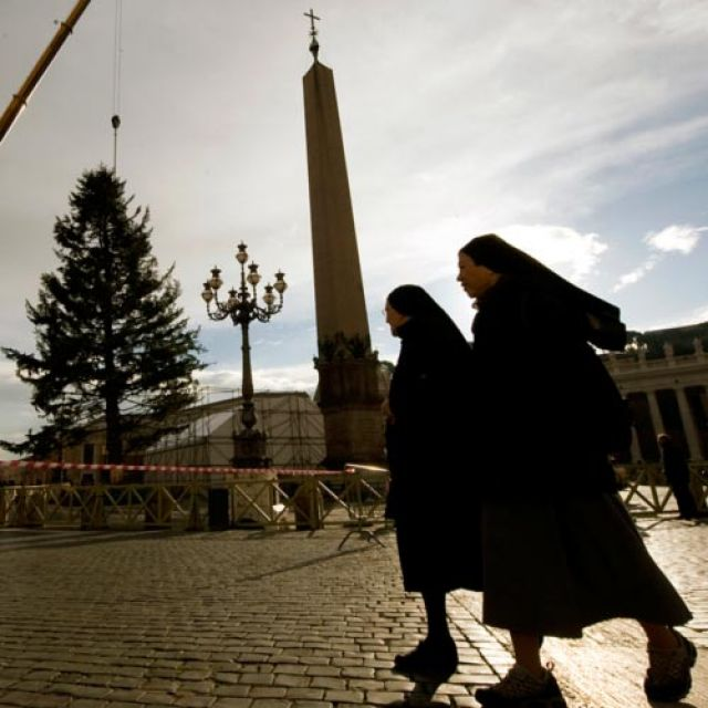 Nuns walk by the Vatican's Christmas tree as it's positioned in St. Peter's Square at the Vatican Dec. 6. The tree is a 78-foot silver fir from the southern Italian region of Molise.