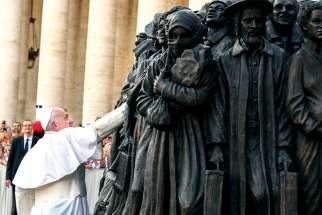 Pope Francis touches the piece after overseeing its unveiling in St. Peter's Square on Sept. 29.
