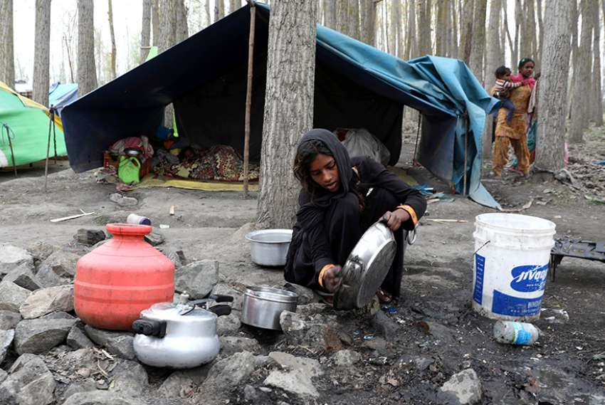 A girl washes utensils in late March outside a temporary shelter near Kashmir, India.
