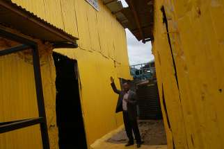 Pastor Steve Shirima, the leader of Jesus Is the Key of Life, a Pentecostal church, explains how his church was painted yellow. The church is deep within the shacks of a slum.