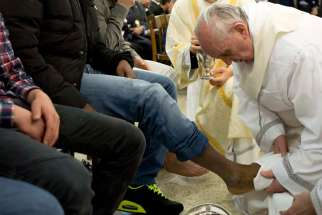 Pope Francis washes the foot of an inmate during the Holy Thursday Mass at Casal del Marmo prison for minors in Rome in this March 28, 2013, file photo. Following a request by Pope Francis, the Vatican issued a decree Jan. 21 specifying that the Holy Thursday foot-washing ritual can include women.