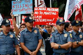 Philippine police keep watch as protesters hold signs against martial law extension in Mindanao Dec. 13. Congress approved a request by President Rodrigo Duterte to extend martial law across the region until Dec. 31, 2018.