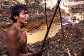 A Yanomami Indian stands near an illegal gold mine during a Brazilian government operation against illegal gold mining on Indigenous land in the heart of the Amazon rainforest.