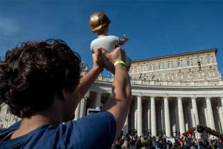 A pilgrim holds up a figurine of the Christ Child as Pope Francis leads the Angelus from the window of his studio overlooking St. Peter's Square at the Vatican Dec 15, 2019.