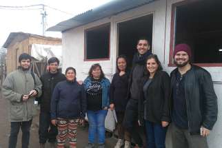 Volunteers from Jesuit-run TECHO-Chile (A Roof for Chile) pose for a photo with community members near a new community center in Rivera Sur camp in Colina, Chile. Young Chileans are discovering that helping others can help them reignite their faith.