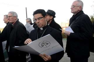 Bishop Oscar Cantu of Las Cruces, N.M., looks at documents explaining the proposed Israeli security wall in the West Bank's Cremisan Valley Jan. 13. Bishop Cantu is part of the Holy Land Coordination visit for bishops from Europe and North America.